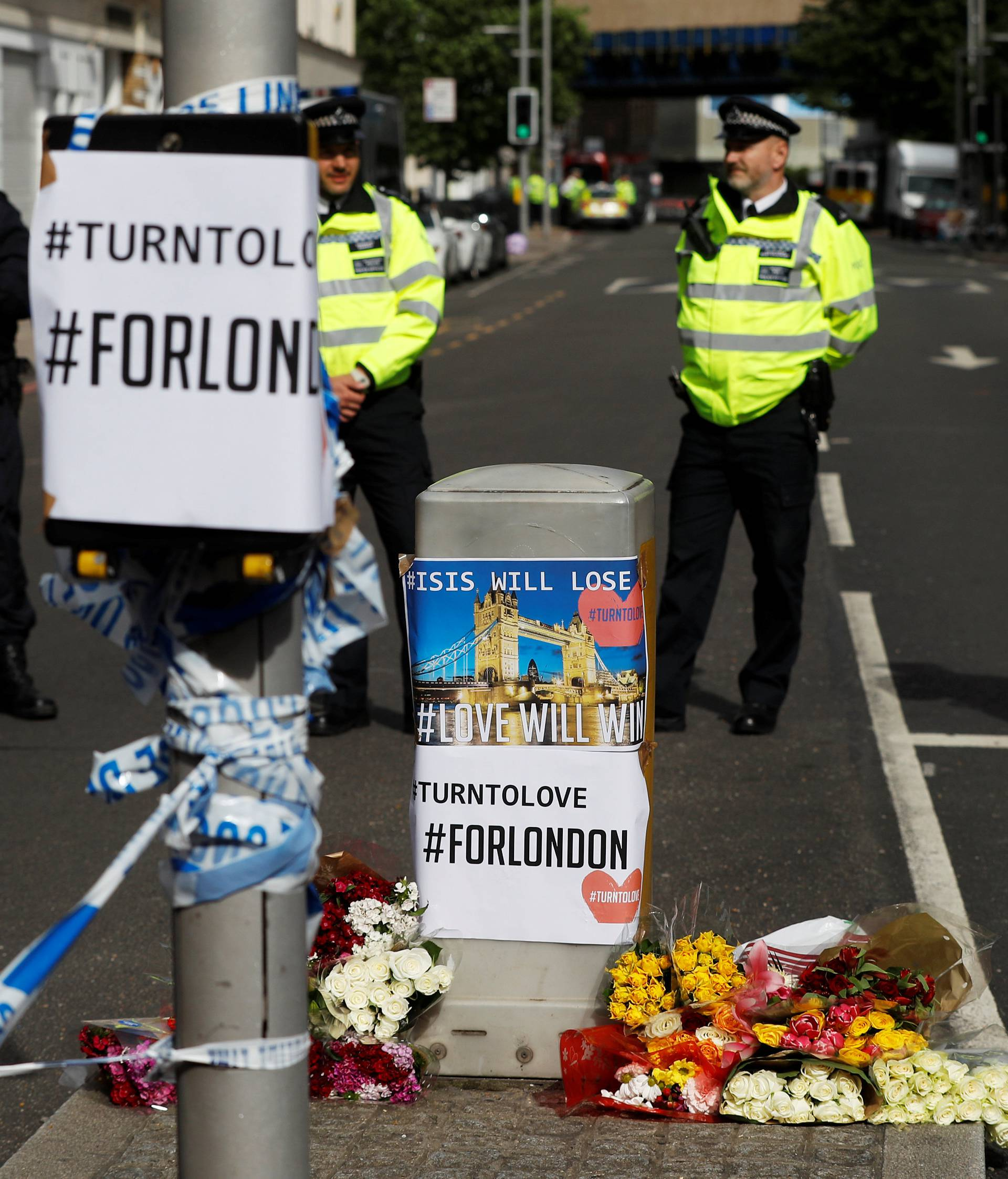 Flowers and messages lie behind police cordon tape near Borough Market after an attack left 7 people dead and dozens injured in London