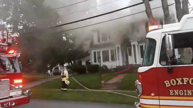 Still image from social media video footage by Boston Sparks shows firefighters working near a building emitting smoke after explosions in North Andover, Massachusetts