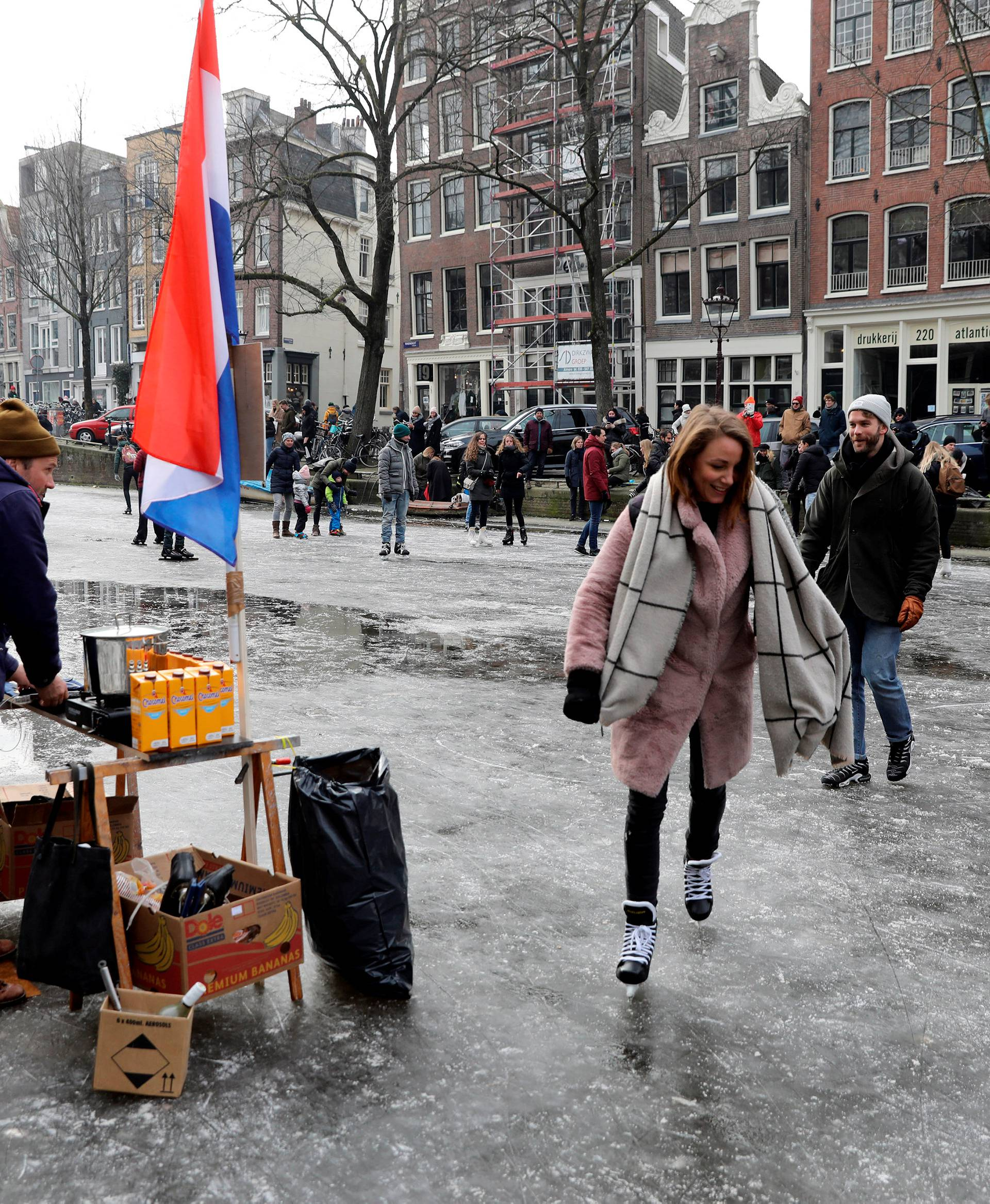 A vendor of hot chocolate watches as ice skaters skate and walk on the frozen Prinsengracht canal during icy weather in Amsterdam