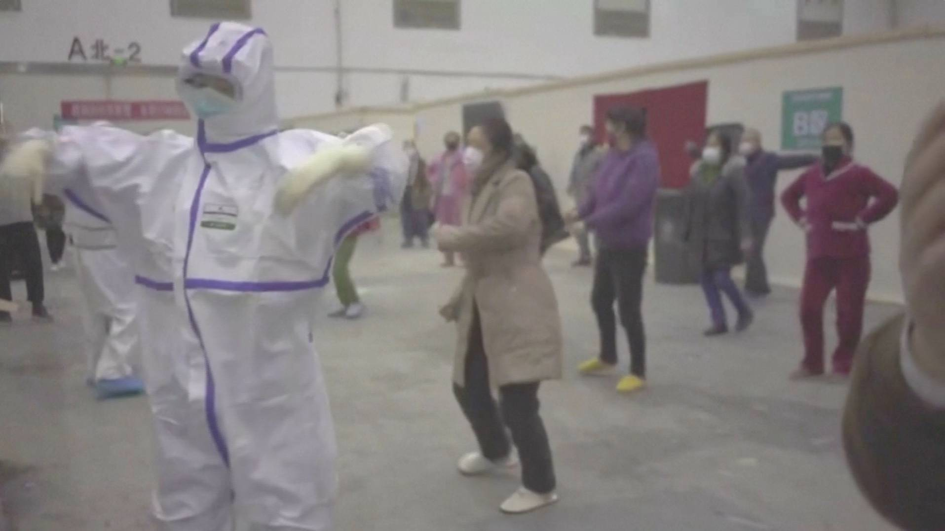 Coronavirus patients and medical staff dance to a lively Chinese song about red flowers at a makeshift hospital in Wuhan, China in this still frame obtained from video