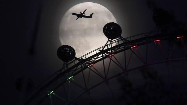 "An aeroplane flies past the London Eye wheel, and moon, a day before the ""supermoon"" spectacle in London"