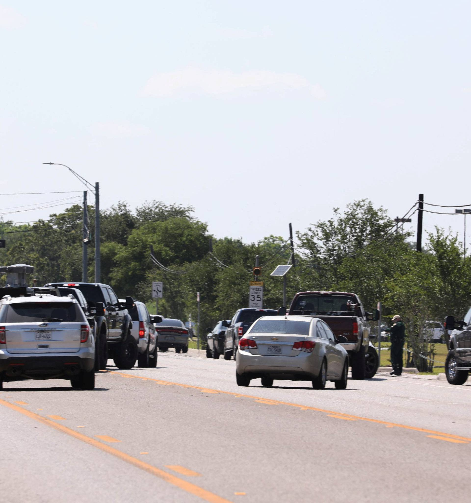 Police keep a roadblock in front of the Santa Fe High School after police found explosives at the school where shooting left several people dead in Santa Fe Texas