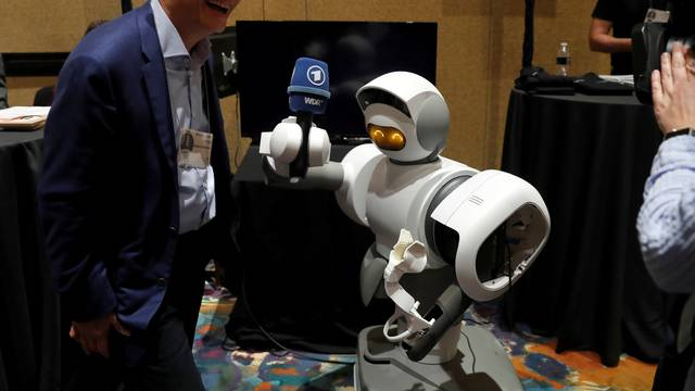 A home assistant robot holds a microphone for Alexander Huang, founder and CEO of Aeolus Robotics during Pepcom's Digital Experience in Las Vegas