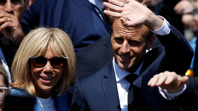 French President Emmanuel Macron waves to the crowd while touring Old Montreal with his wife Brigitte Macron in Montreal