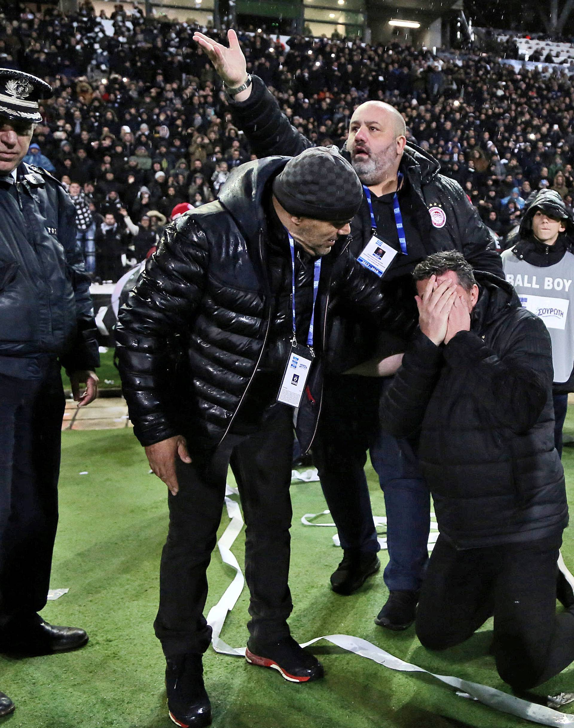 Olympiacos coach Oscar Garcia reacts after his injury during a Greek Super League soccer match between PAOK and Olympiacos in Thessaloniki