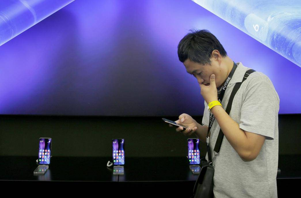 A journalist stands next to a poster of Xiaomi Mi MIX Alpha surround display 5G concept smartphone in Beijing