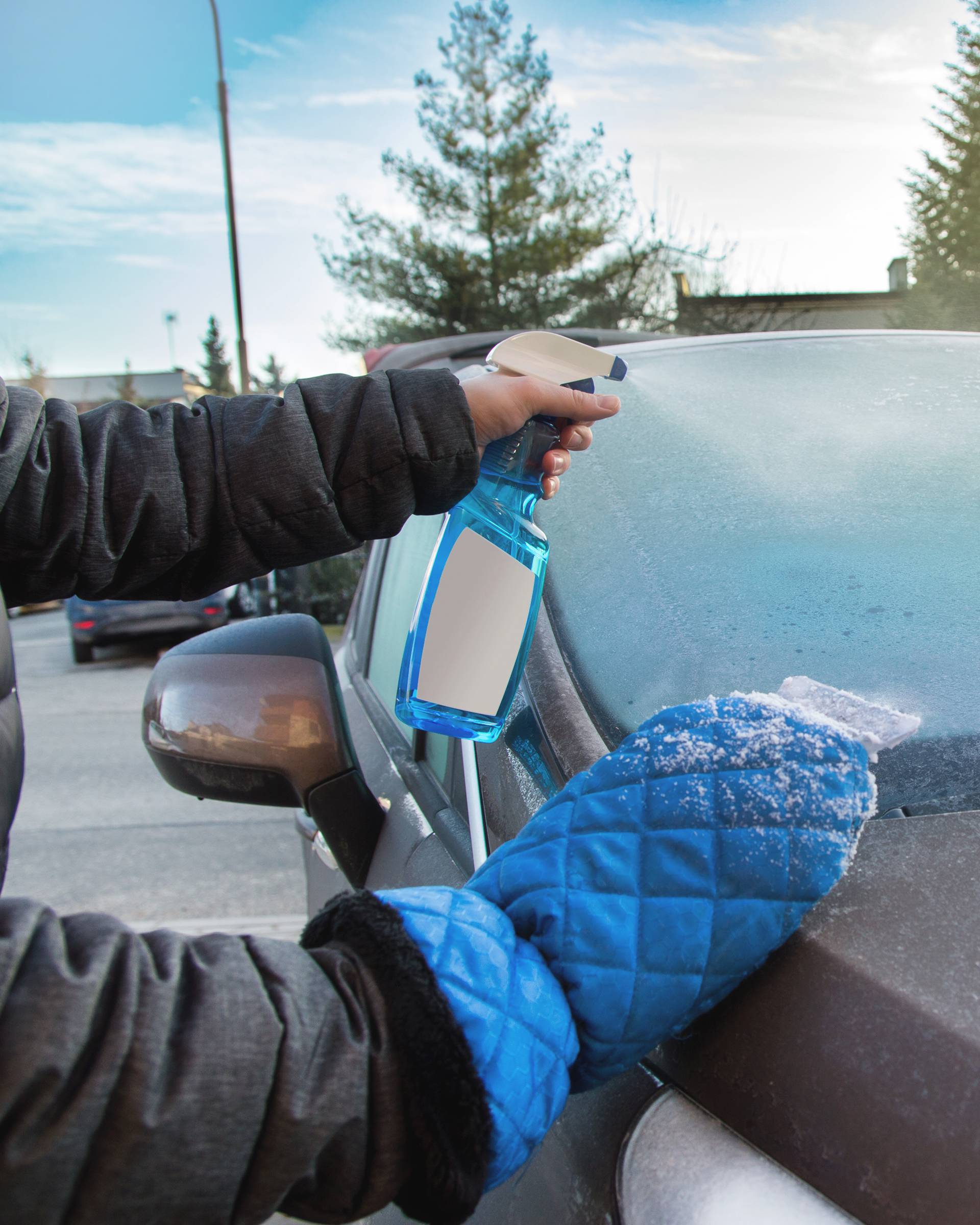 Man uses defroster spray to remove frost