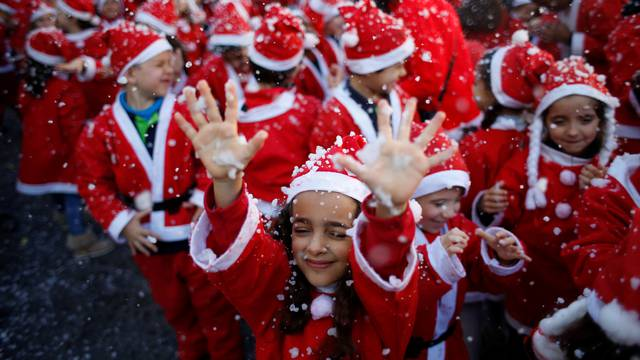 Children dressed as Santa Claus participe in a parade held to collect food for the needy, in Lisbon