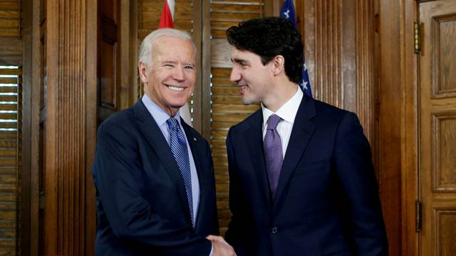 FILE PHOTO: Canada's PM Trudeau shakes hands with U.S. Vice President Biden during a meeting in Trudeau's office on Parliament Hill in Ottawa