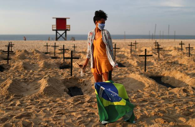 An activist of the NGO Rio de Paz wearing a protective mask attends a demonstration during which one hundred graves were dug on Copacabana beach symbolising the dead from the coronavirus disease (COVID-19), in Rio de Janeiro