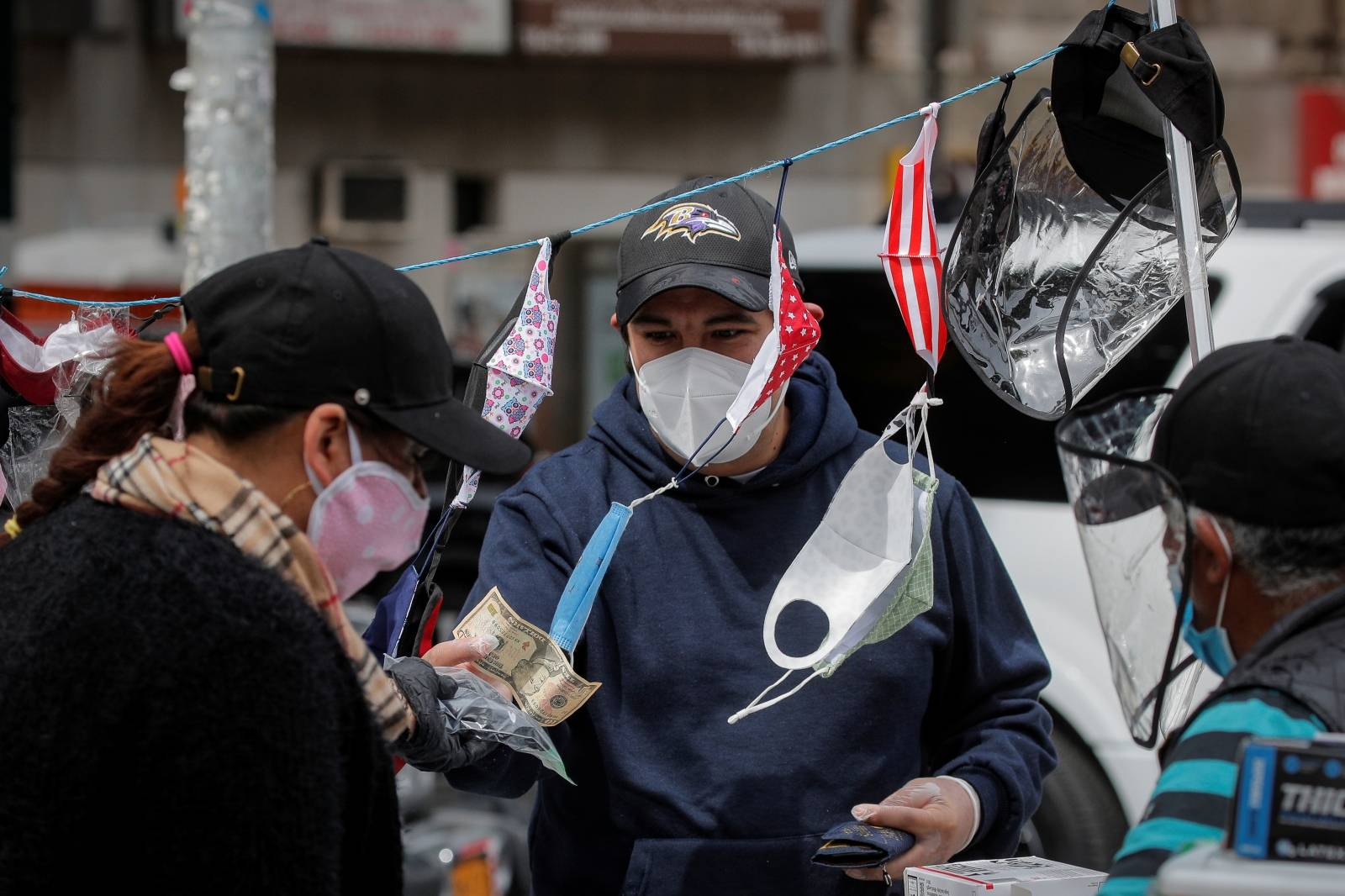 A man purchases a face mask from a street vendor, during the outbreak of the coronavirus disease (COVID-19), in the Corona section of Queens, New York
