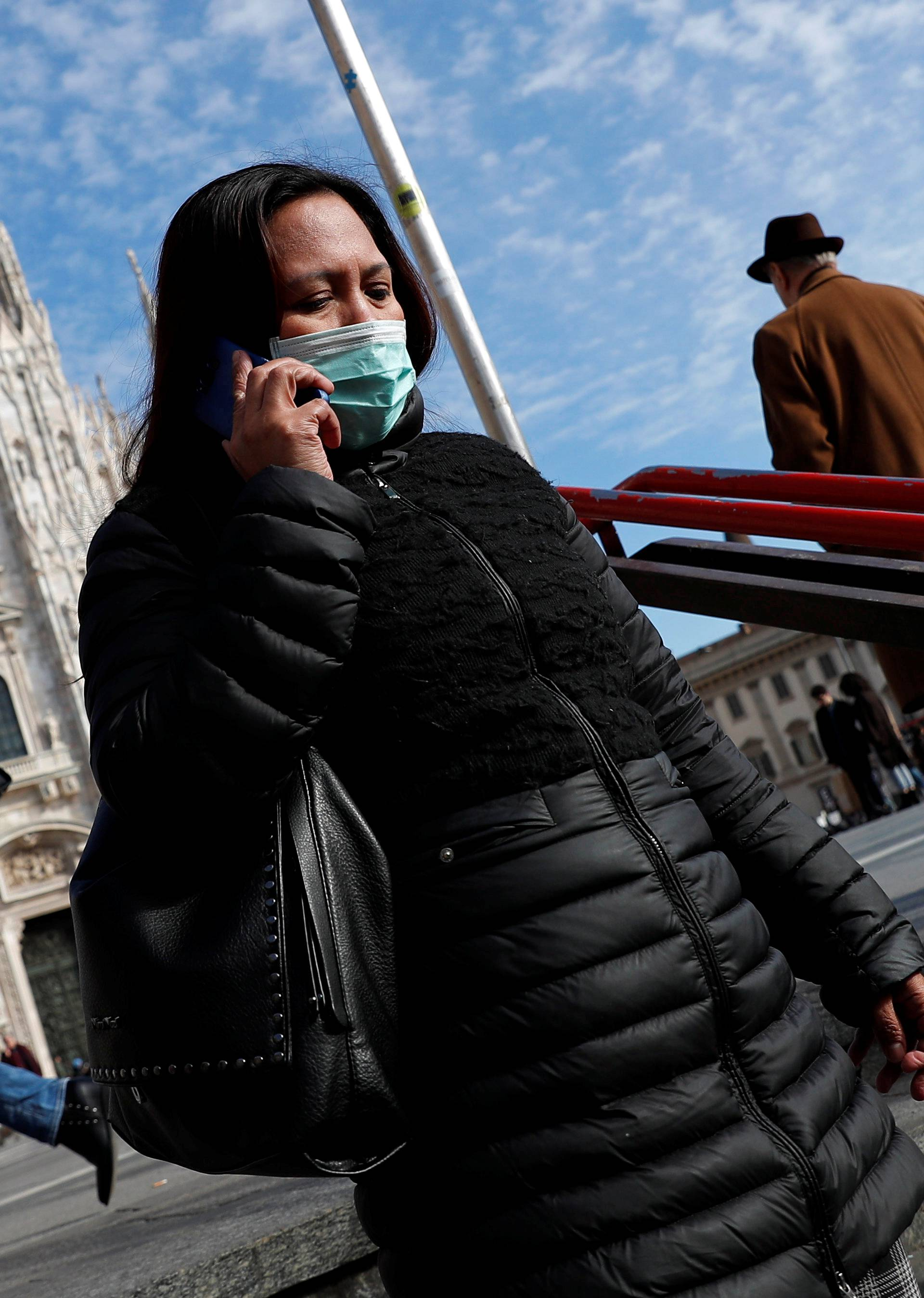 A woman wearing a protective face mask to prevent contracting the coronavirus enters a subway station in Milan
