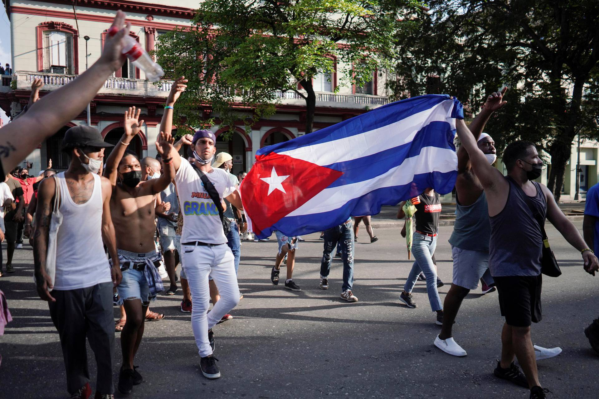 People hold Cuba's national flag during protests against and in support of the government, in Havana