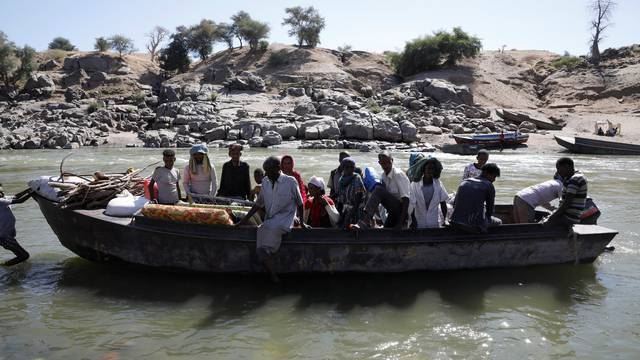 Ethiopians fleeing from the Tigray region arrive by boat to Sudan, near the Hamdayet refugee transit camp
