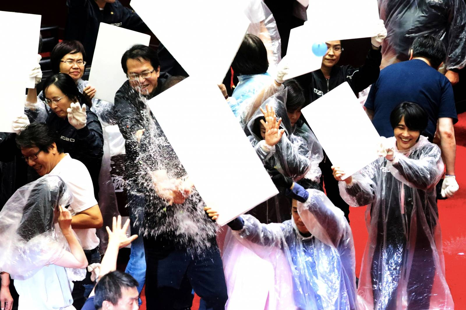 Lawmakers from Taiwan's ruling Democratic Progressive Party (DPP) with lawmakers from the main opposition Kuomintang (KMT) party throw water balloons at each other inside the parliament in Taipei