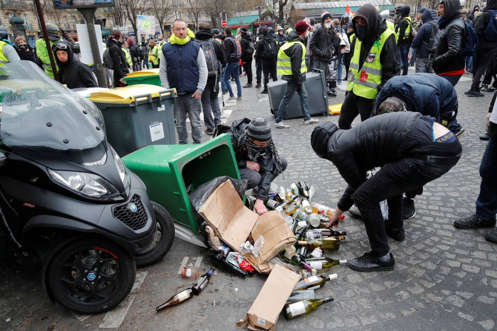 """Protesters pick up bottles during a demonstration by the """"yellow vests"""" movement in Paris"""