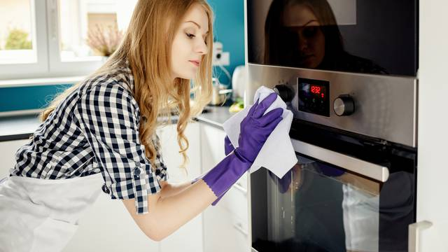 Beautiful blonde woman polishes stainless steel oven