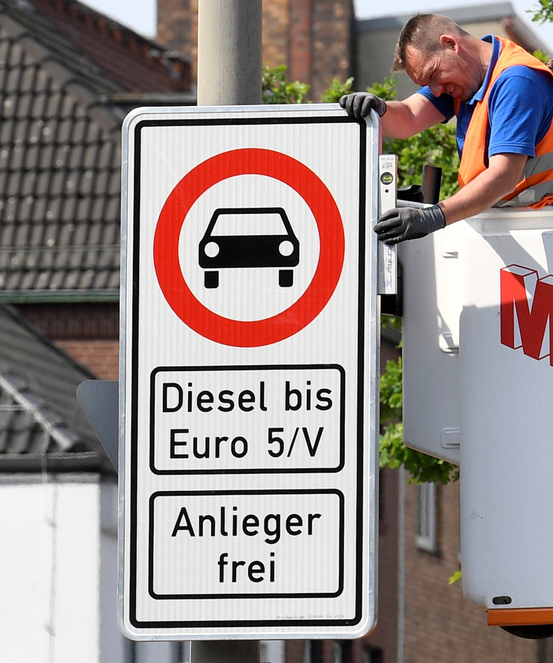 FILE PHOTO: Traffic signs which ban diesel cars are installed by workers at the Max-Brauer Allee in downtown Hamburg