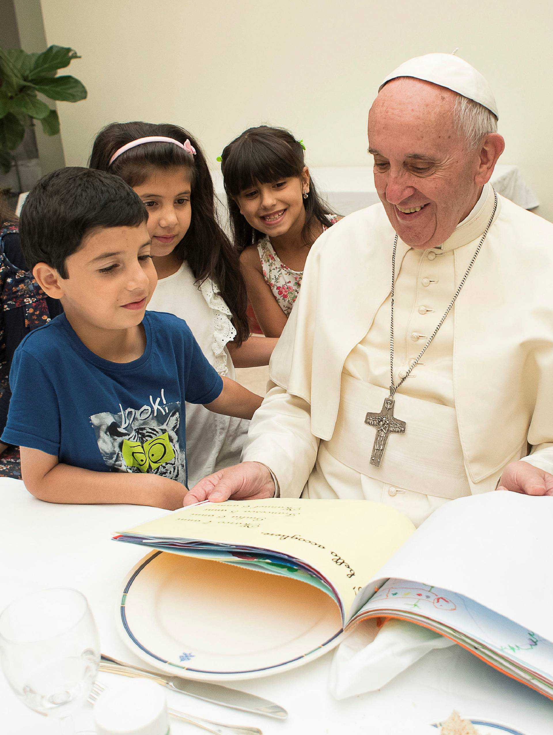 Pope Francis sits with some Siryans refugees at the Vatican