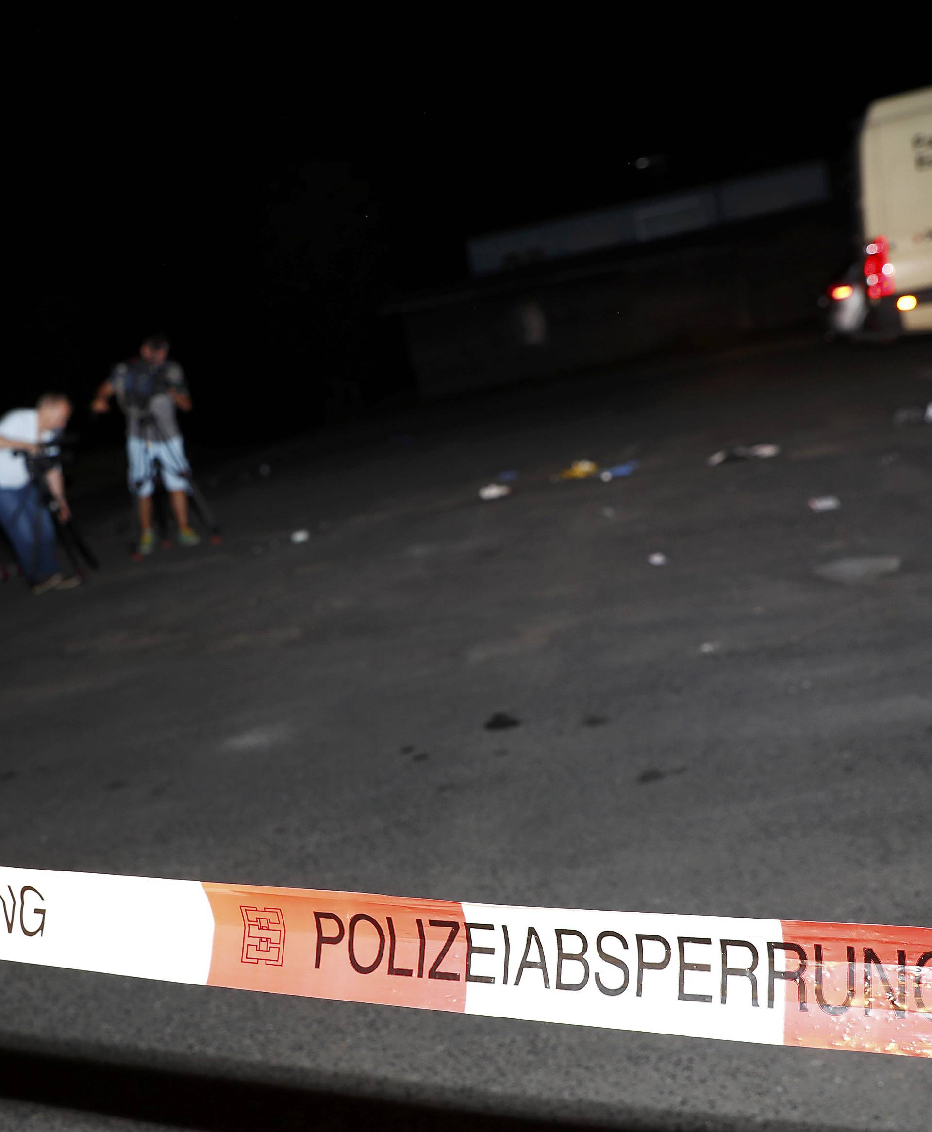 Cameramen film at the scene where a man was shot dead by the police after attacking passengers on a train with an axe near the city of Wuerzburg