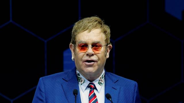 Singer Elton John speaks after receiving a Crystal Award from Hilde Schwab, Chairperson and Co-Founder, Schwab Foundation for Social Entrepreneurship, during the World Economic Forum (WEF) annual meeting in Davos