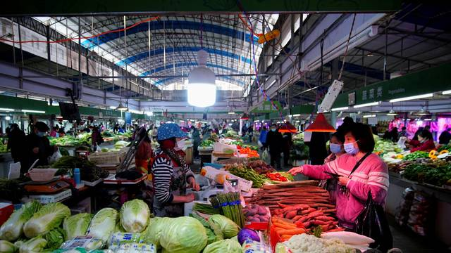 People wearing face masks buy vegetables at a wet market, following an outbreak of the coronavirus disease (COVID-19) in Wuhan