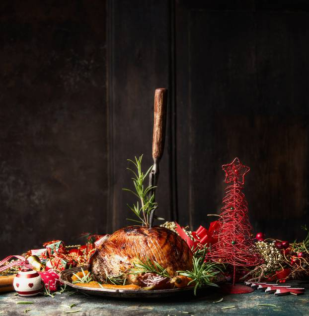 Christmas ham with stuck fork and rosemary on table with festive