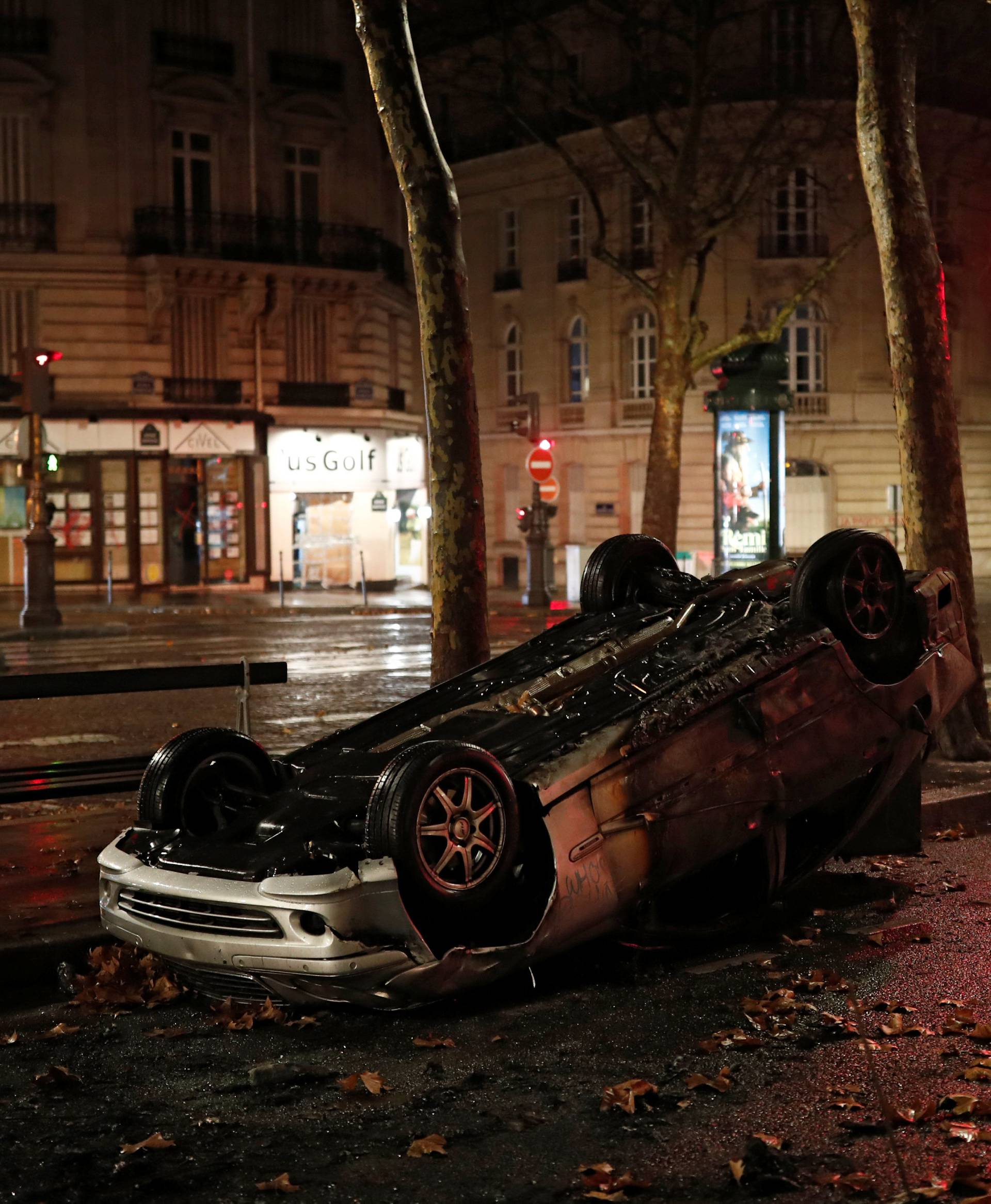 A vandalized car is seen on a street the morning after clashes with protesters wearing yellow vests, a symbol of a French drivers' protest against higher diesel taxes, in Paris