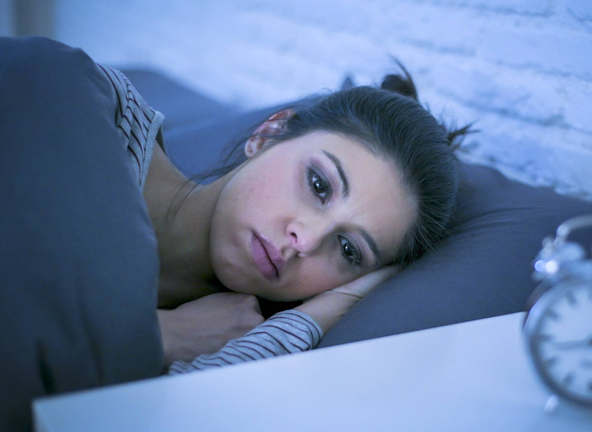 young beautiful sad and worried latin woman suffering insomnia and sleeping disorder problem unable to sleep late at night lying on bed awake