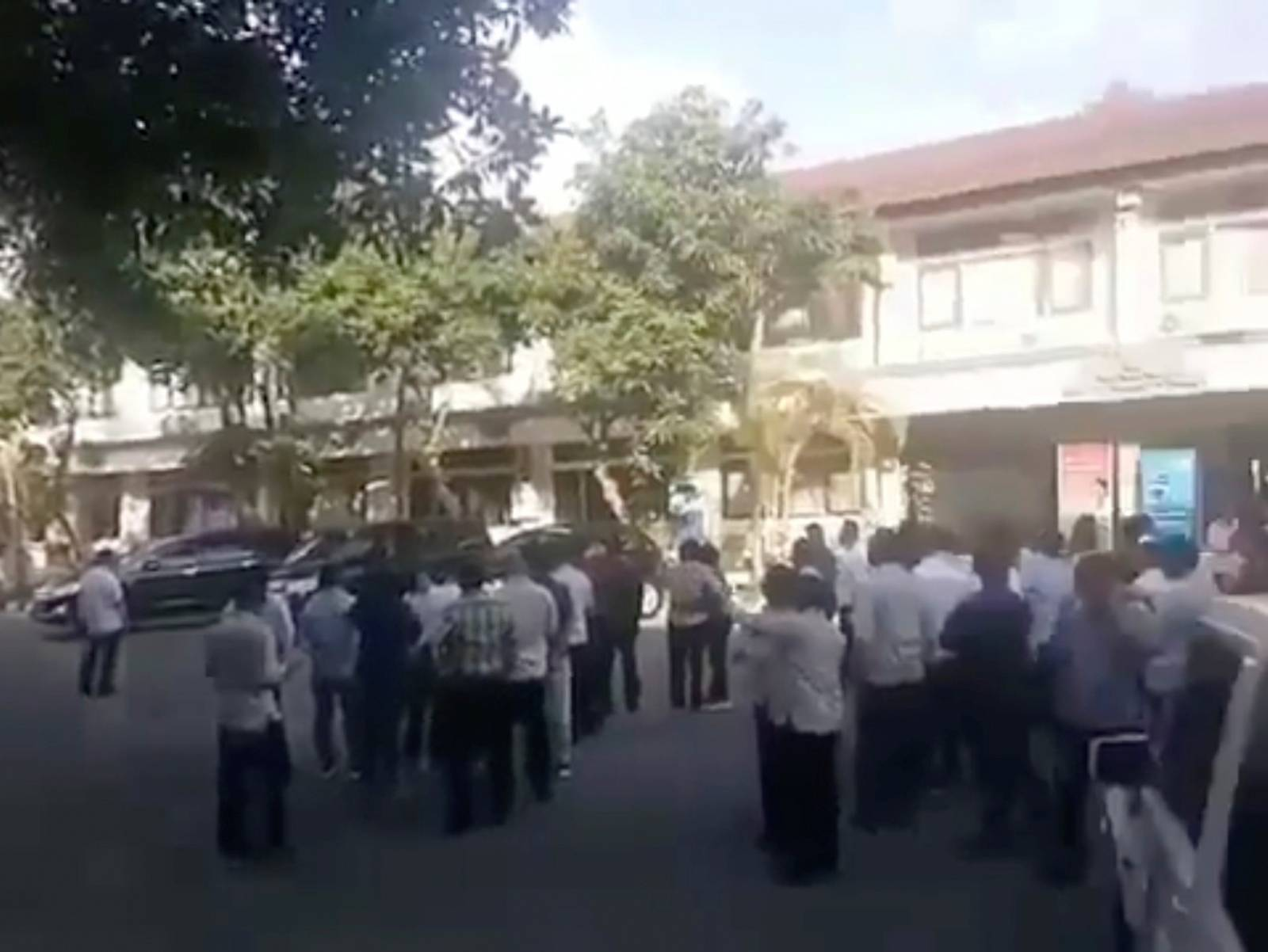 A crowd stands outside a building as an undersea quake struck south of Bali