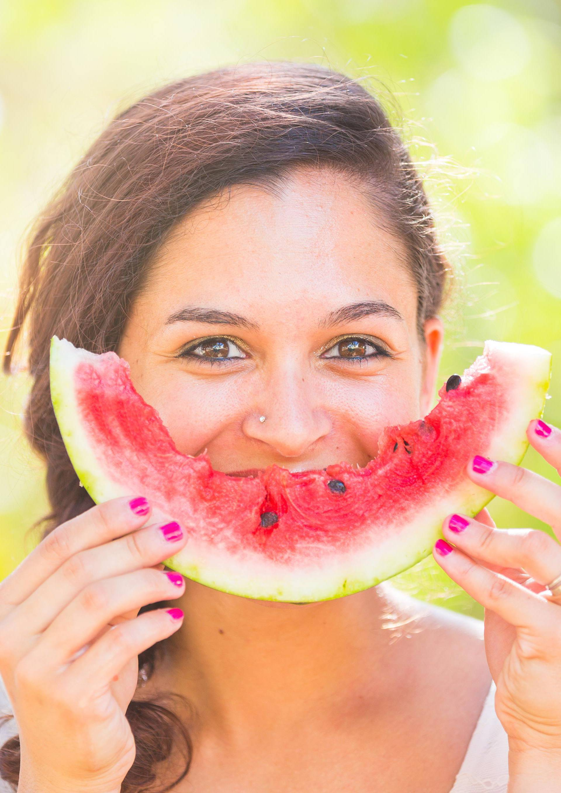 Beautiful young woman at park eating a slice of watermelon
