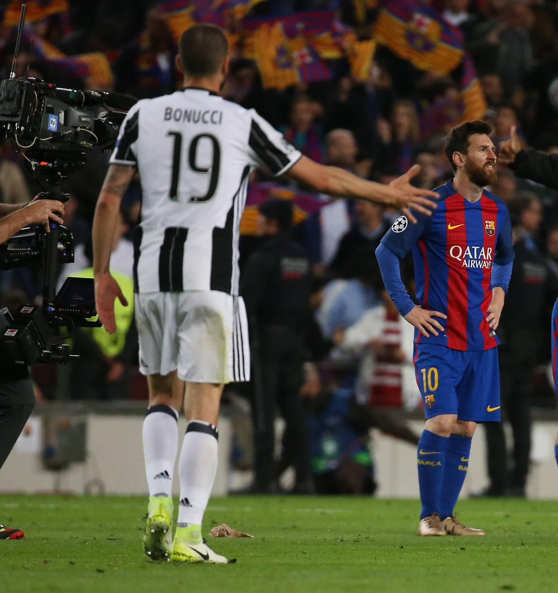Juventus' Leonardo Bonucci and Juan Cuadrado  celebrate after the match as Barcelona's Lionel Messi looks dejected