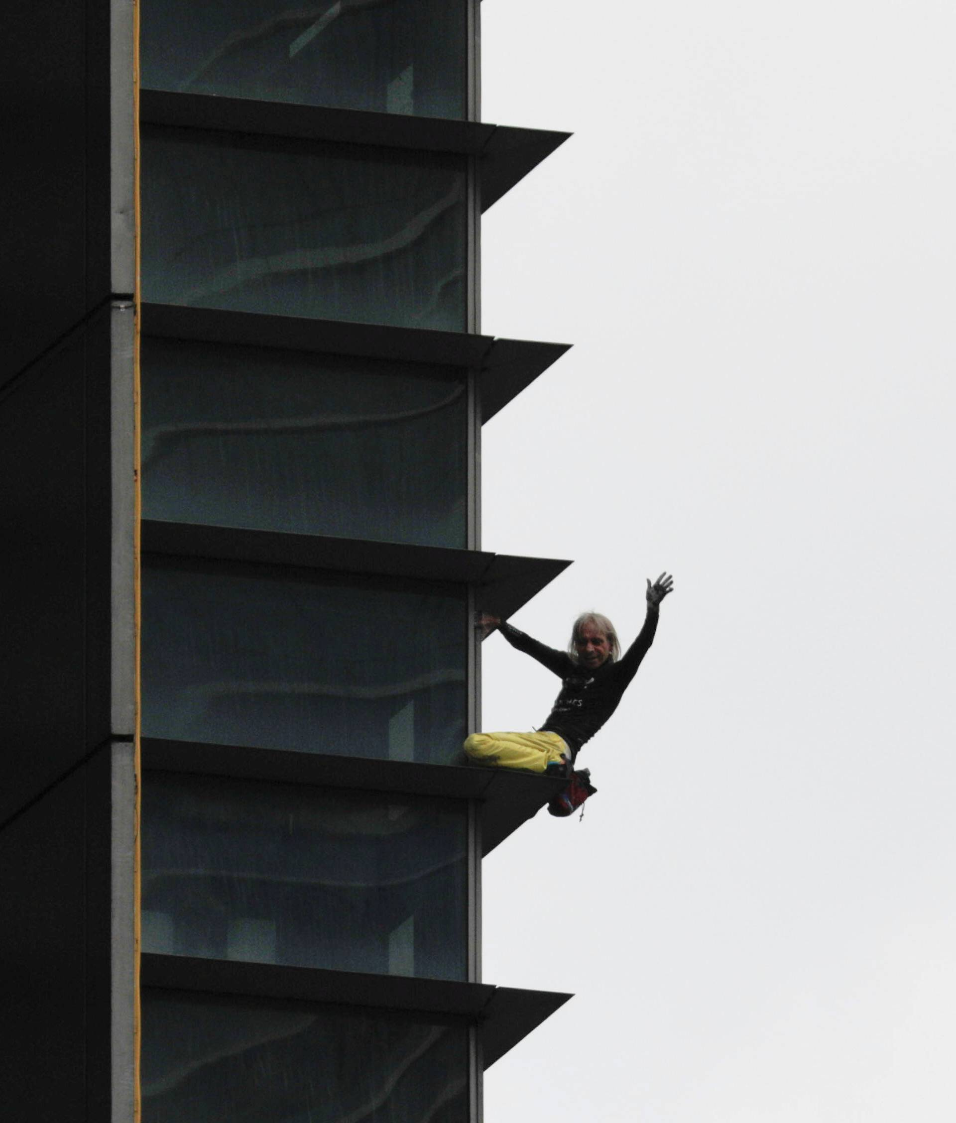 French climber Robert waves as he climbs down the 47-storey GT International Tower in Makati City