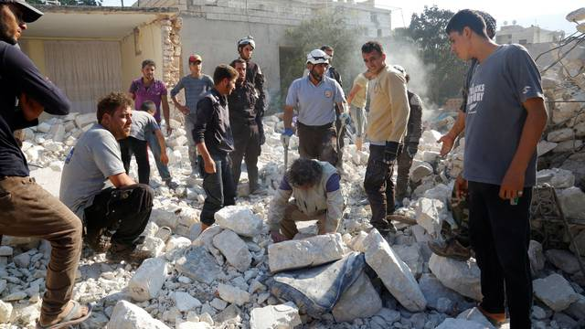 Men and civil defence members look for survivors after an airstrike on a hospital in the town of Meles, western Idlib city in rebel-held Idlib province