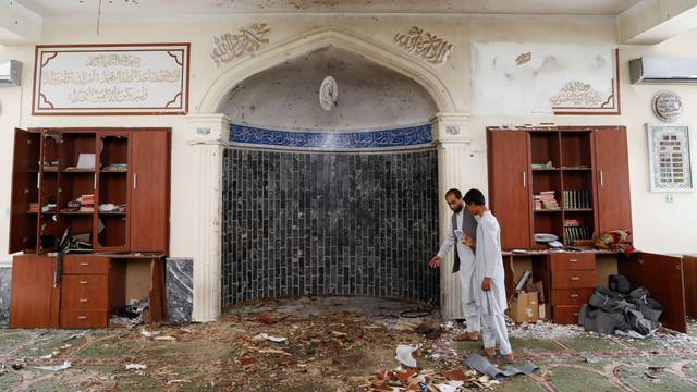 Men inspect the site of a blast inside a mosque in Kabul, Afghanistan