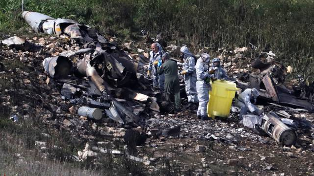 Israeli security forces examine the remains of an F-16 Israeli war plane near the village of Harduf