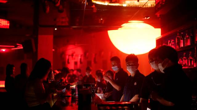 People wear face masks at a nightclub after it reopened in Shanghai
