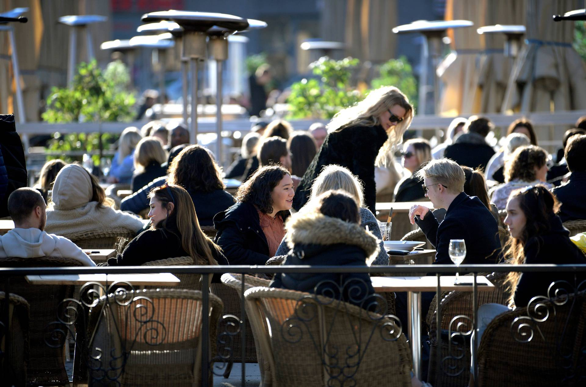 FILE PHOTO: People enjoy the sun at an outdoor restaurant, despite the continuing spread of the coronavirus disease (COVID-19), in Stockholm