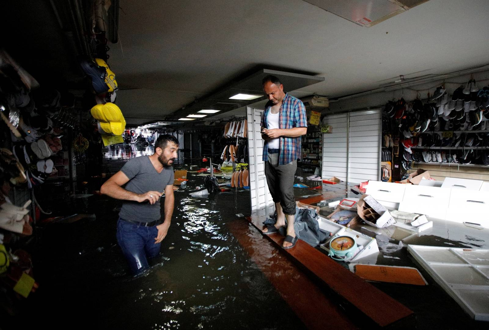 Shopkeepers try to save their goods at a flooded underground passage following heavy rains in Istanbul