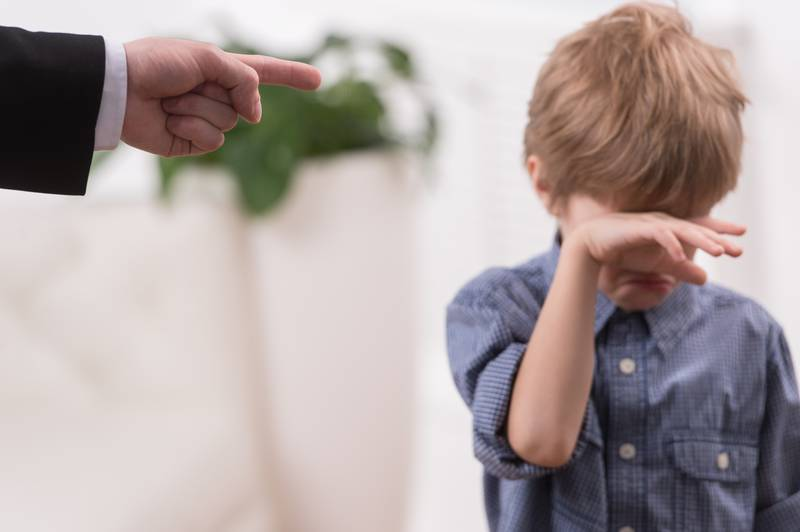 Strict father discipline naughty son. Isolated on white background boy wiping tears