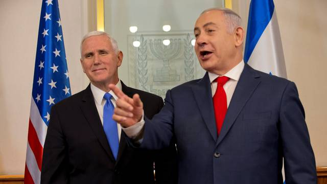 U.S. Vice President Mike Pence stands next to Israeli Prime Minister Benjamin Netanyahu during a meeting at the Prime Minister's office in Jerusalem