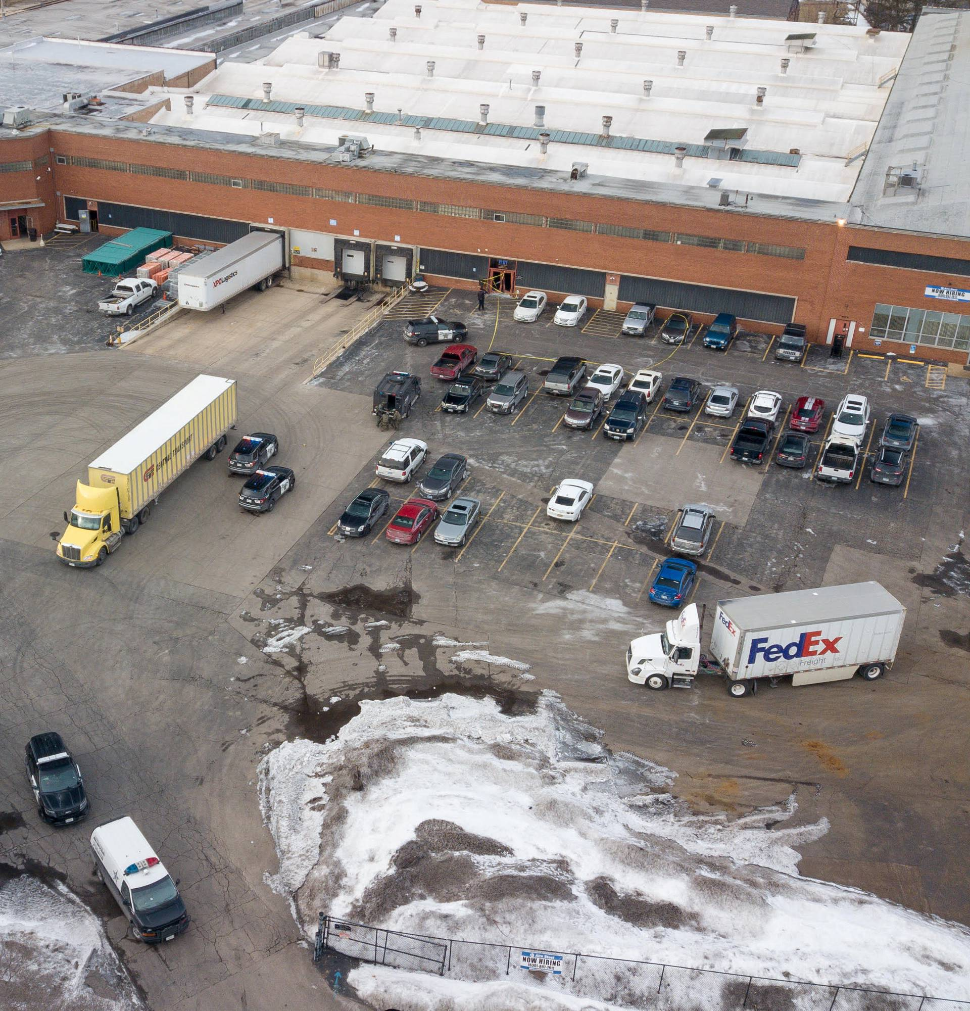 An aerial photo of police and emergency vehicles parked in a lot adjacent to a warehouse at the scene of a mass shooting involving multiply casualties in Aurora, Illinois