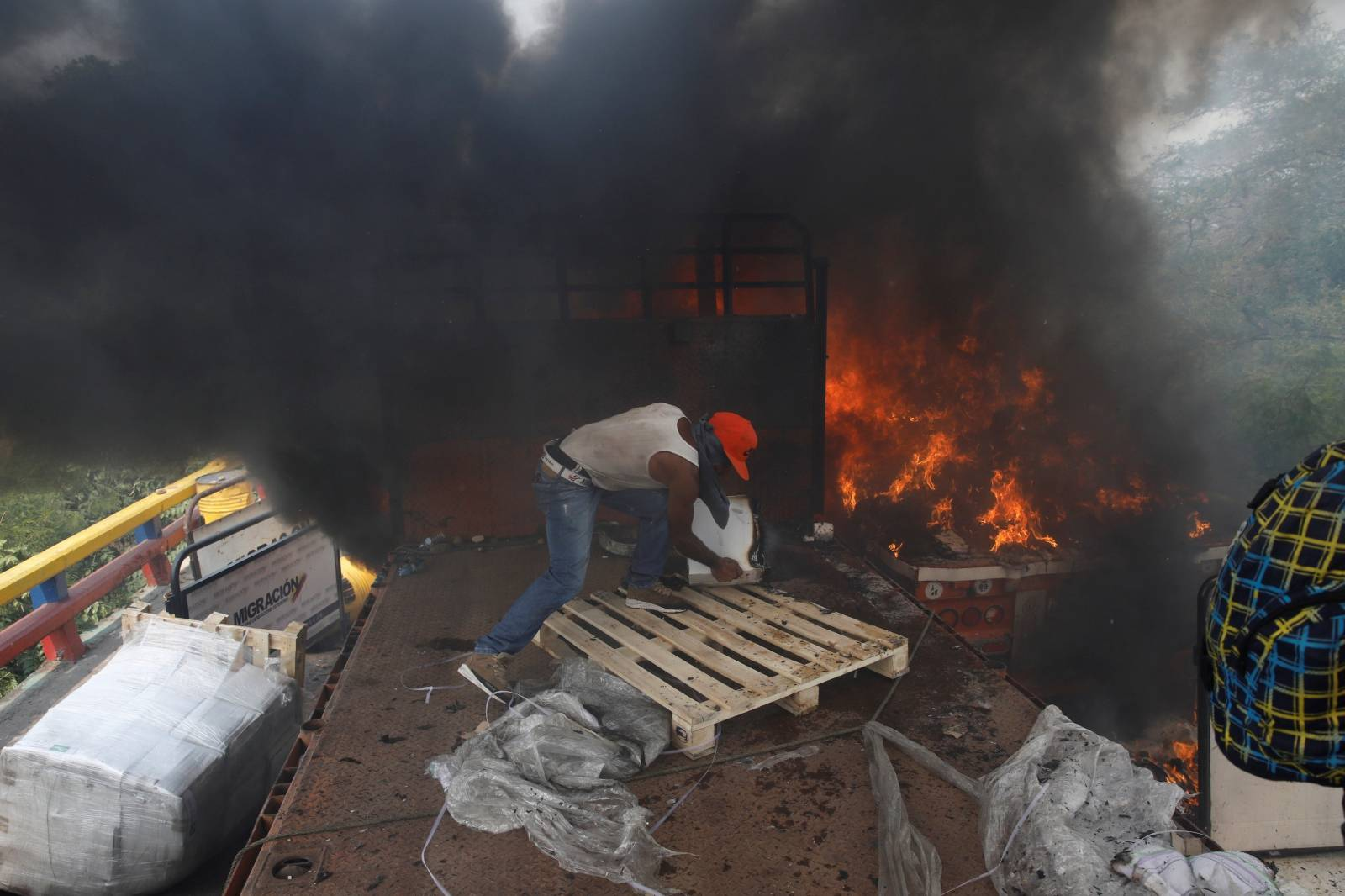 Opposition supporters unload humanitarian aid from a truck that was sent on fire in Cucuta