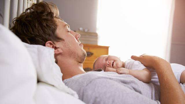 Father Sleeping In Bed Holding Newborn Baby Daughter