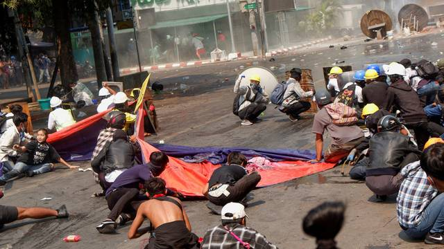 Protesters lie on the ground after police open fire to disperse an anti-coup protest in Mandalay