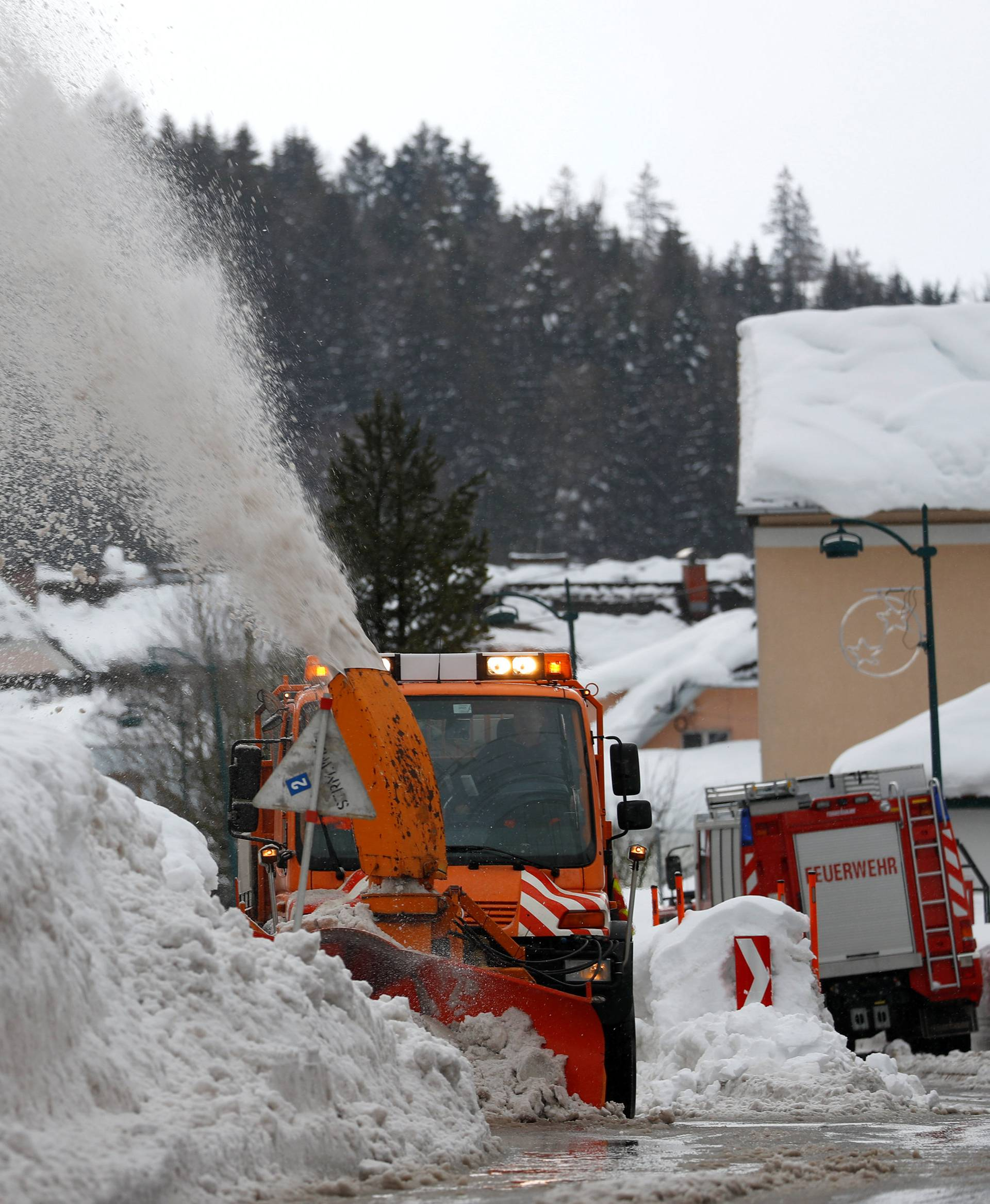A vehicle removes snow on a road after heavy snowfall in Rosenau