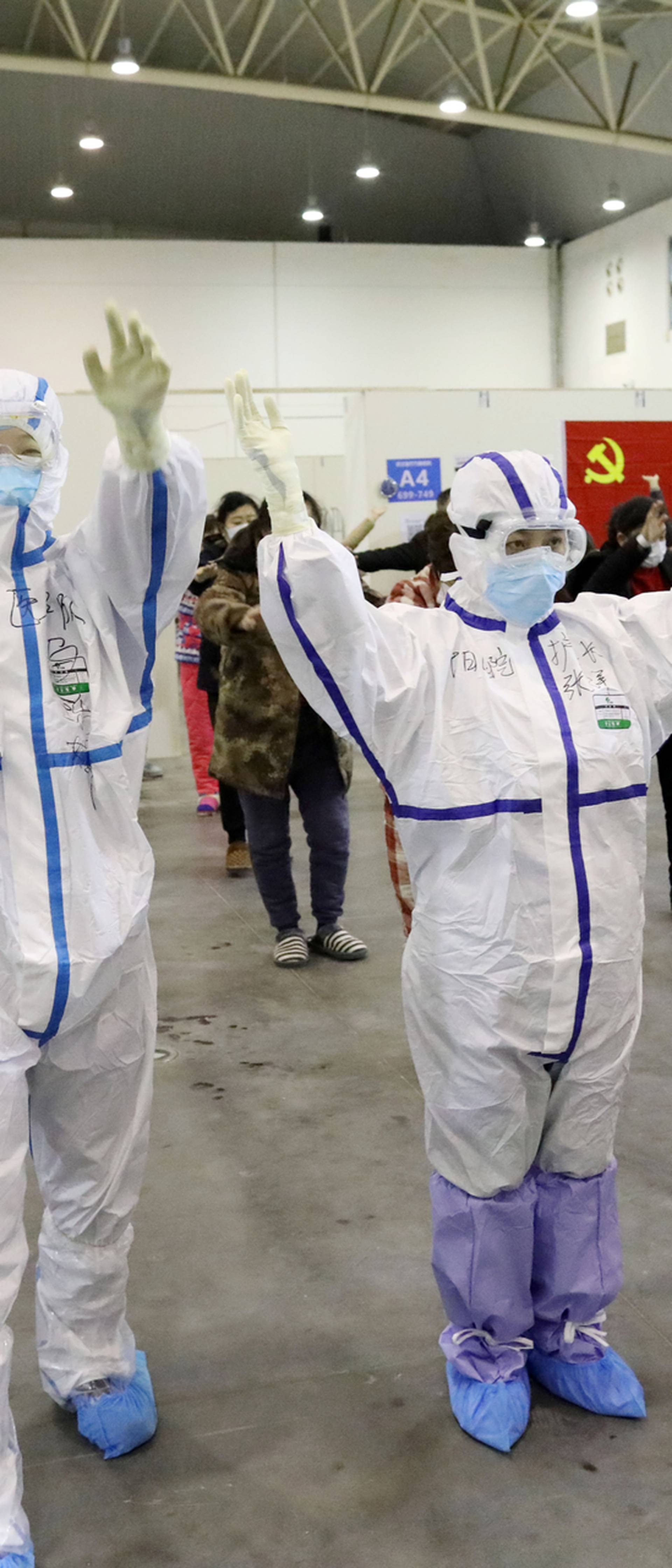 Medical workers in protective suits dance with patients inside the Wuhan Parlor Convention Center that has been converted into a makeshift hospital following an outbreak of the novel coronavirus