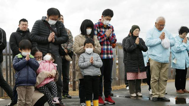 People pray to mourn victims at the time when the magnitude 9.0 earthquake struck off Japan's coast in 2011, in Iwaki, Fukushima prefecture