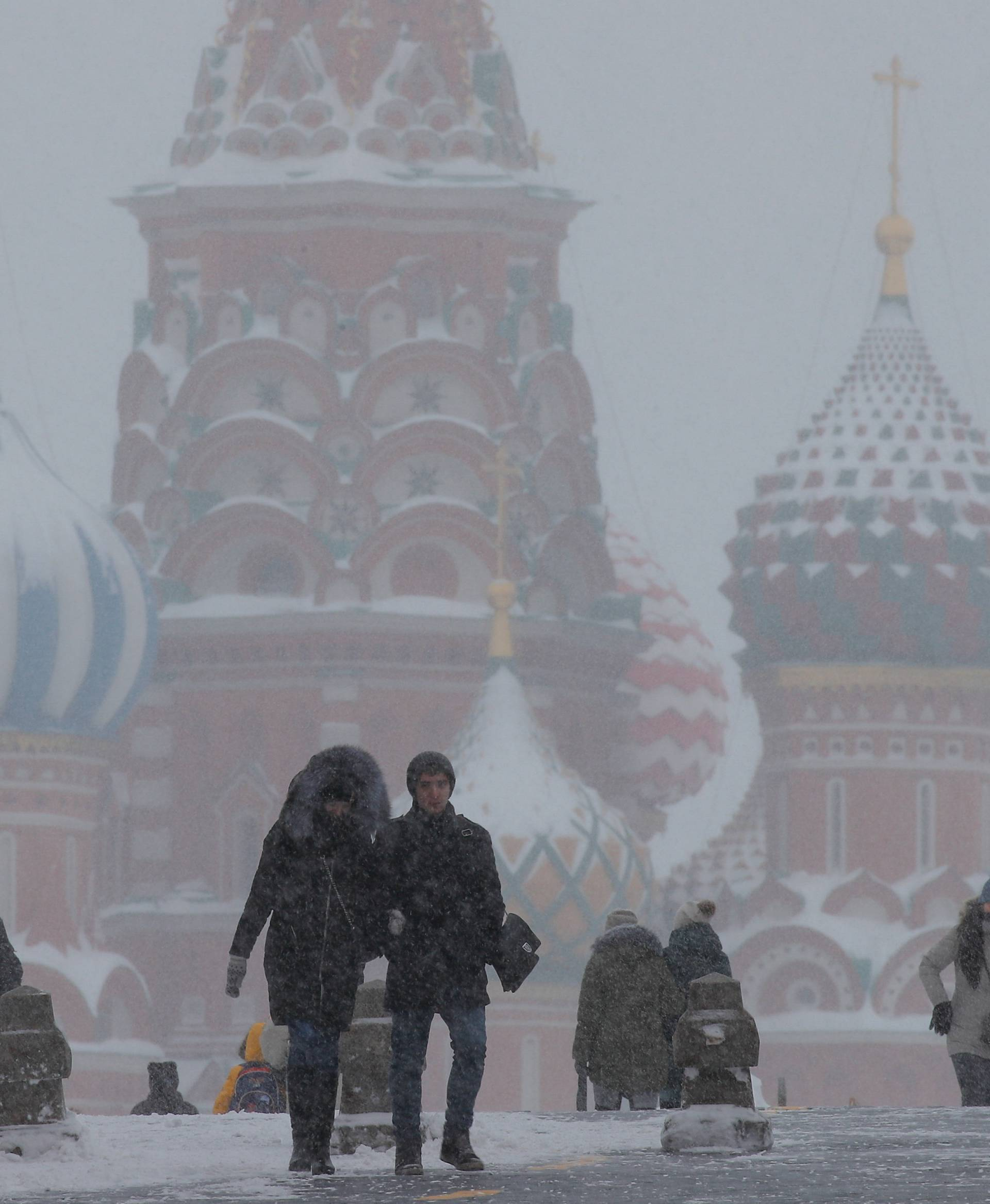 People walk in the Red Square during heavy snowfall in Moscow