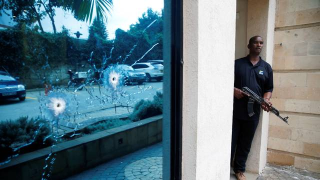 A policeman takes position at the scene where explosions and gunshots were heard at the Dusit hotel compound, in Nairobi